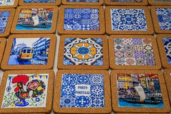 Porto, Portugal - May 31, 2018: Souvenir coasters made with cork wood and traditional ornate azulejo Portuguese ceramic tiles on display at a shop