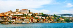 Porto, Portugal. Panoramic view of colorful old houses of Porto, Portugal with Luis I Bridge - a metal arch bridge over Douro River. It is a symbol of the city and a most popular touristic attraction