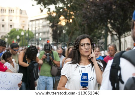 PORTO, PORTUGAL - SEPTEMBER 15: Journalist making report for portuguese national television with protestors against government spending cuts and tax rises in Aliados, Porto on September 15, 2012 in Porto, Portugal