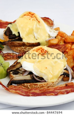 Portobello mushroom brie eggs benedict with bacon and fruits on side