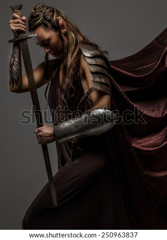 Stock Photo Portrai of mystic  elf woman with sword, armor and tattoo on her hand. A side view portraite.