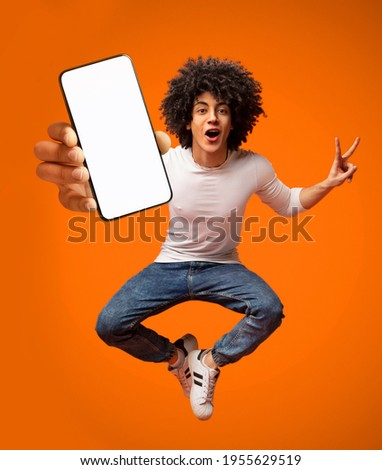 Portraif of excited African American teen guy jumping with smartphone, demonstrating empty screen on orange background, copy space for your mobile advertisement, mockup image
