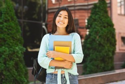 Portraif of smiling asian student girl with backpack and workbooks posing over college campus background, looking at camera, free space