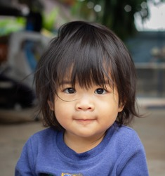 Portrait, a baby, an Asian woman toddler with bangs hair cheerful, is so adorable child, wearing a blue sweater, smiling at the camera.