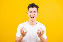 Portrait Aaian handsome young man standing wearing white t-shirt he expressions irate, angry face screaming, studio shot isolated yellow background