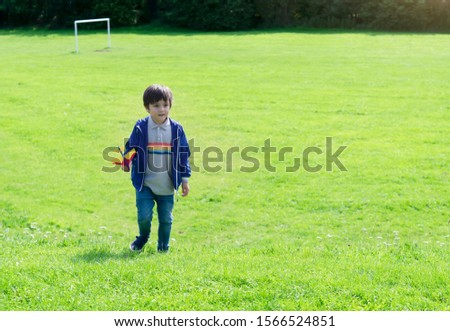 Portrait active little boy playing with toy airplane against green nature background, Child throwing foam airplane in green field , Kid playing in the park,  Childhood outdoor activity concept #1566524851