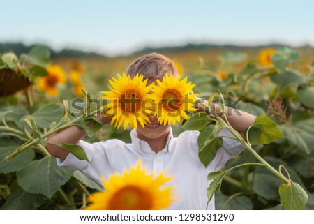 Portrait adorable child with sunflower in summer sunflower field. Kids happiness concept