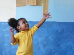 Portrait Afican American child is grabbing something.