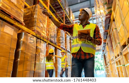 Portrait african black warehouse supervisor standing with digital tablet check stock in large warehouse distribution center with colleague worker in background. Business warehouse and logistic concept