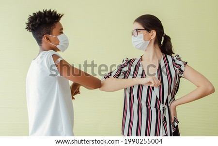 Portrait African man and Caucasian young woman making elbow bump or hit, wearing face masks, getting vaccination to protect covid19 rus with bandage on shoulder, looking each other with confidence Stok fotoğraf ©