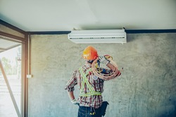 Portrait  air conditioner technician or air-conditioning installation technician is about to repair air conditioning in homes and buildings.Air conditioner repairmen work on home unit.
