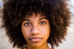 portrait and close up of beautiful young African or American woman looking at the camera