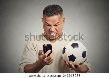 Portrait angry frustrated man looking on cell smart phone watching game holding football displeased isolated grey wall background. Negative emotion, face expression feelings. Data plan online gaming