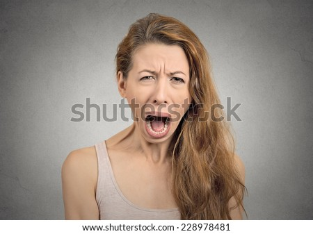 Portrait angry upset woman screaming crying wide open mouth hysterical face grimace isolated grey wall background.Negative human expression emotion bad feeling reaction. Conflict confrontation concept
