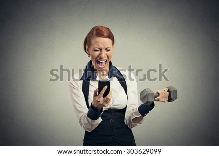 Portrait angry young business woman screaming on mobile phone lifting dumbbell