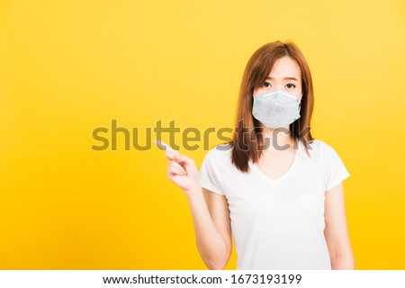 Portrait Asian beautiful happy young woman wearing face mask protects filter dust pm2.5 anti-pollution, anti-smog, and air pollution her pointing out to side on yellow background, with copy space