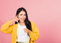 Portrait Asian beautiful young woman smiling doing phone gesture with hand fingers on telephone and pointing to camera while making call back to me gesture, studio shot isolated pink background