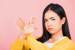 Portrait Asian beautiful young woman unhappy or confident standing wear holding two cross arms say no X sign, studio shot isolated pink background, Thai female pose reject gesture with copy space