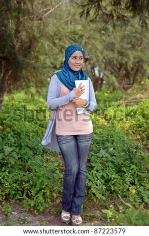 Portrait asian female Muslim student holding books