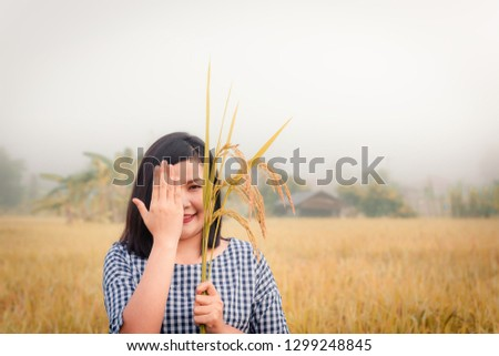 Portrait asian woman is holding bundle of rice in the rice fields., Happy woman has enjoying in organic farming of countryside., Outdoor and leisure activities.