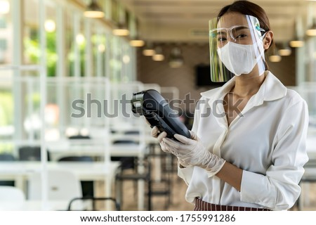 Portrait attractive asian waitress wear face mask and face shield hold credit card reader for contactless payment with indoor restaurant background. New normal restaurant contactless payment concept.