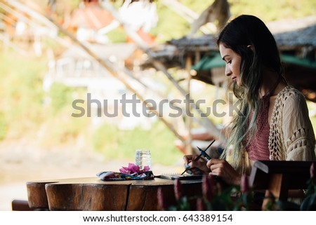 Stock Photo Portrait attractive brunette woman sitting at wooden table in summer cafe and looking at the album. Close up beautiful young brunette painter draws in album in outdoor summer cafe