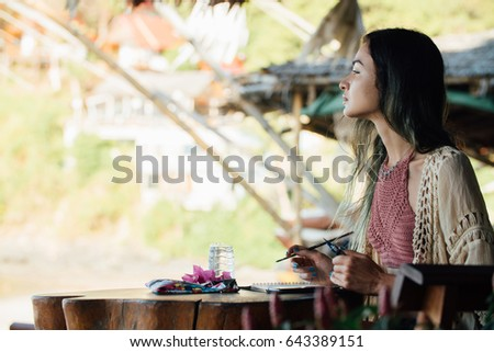 Stock Photo Portrait attractive brunette woman sitting at wooden table in summer cafe and looking into distance. Close up beautiful young brunette painter draws in album in outdoor summer cafe
