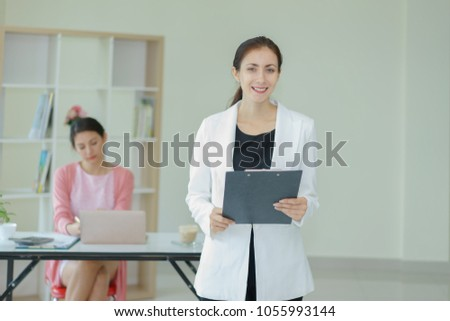 Portrait attractive businesswoman at office.young businesswoman holding document file on hand #1055993144