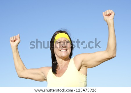 Portrait attractive fit and healthy mature woman outdoor positive smiling and confident with arms up, isolated with blue sky as background and copy space.