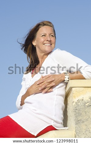 Portrait Attractive happy middle aged woman posing relaxed outdoor, enjoying active retirement, isolated with blue sky as background and copy space.
