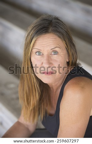 Portrait attractive mature woman sitting alone and lonely, sad thoughtful facial expression, upward look, blurred background.