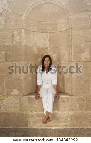 Portrait attractive mature woman sitting alone, lonely and with sad facial expression in alcove at big brick wall.