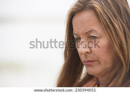 Portrait attractive mature woman with angry, stressed, sad, worried or depressed facial expression, bright outdoor background and copy space.