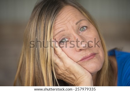 Portrait attractive mature woman with bored, stressed, lonely, depressed and sad facial expression, blurred background.