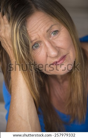 Portrait attractive mature woman with sad, depressed and stressed facial expression, worried, blurred background.