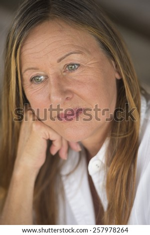 Portrait attractive mature woman with serious sad facial expression, thoughtful, blurred background.