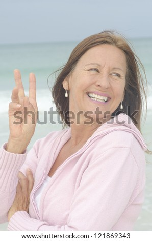 Portrait attractive middle aged woman enjoying active retirement, happy smiling, isolated with ocean as blurred background.