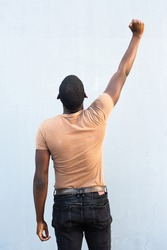 Portrait back of young black man with arm raised and fist pump