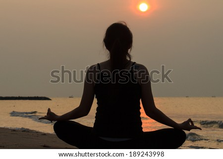 portrait back view of Asian woman practicing yoga at peace sea in morning