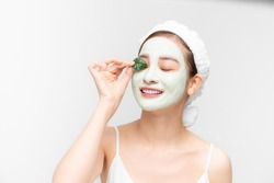 Portrait beautiful Asian woman in towel on head applying white nourishing mask or creme on face, green leaf in hand isolated white background