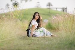 portrait beautiful asian women happy smile and relax sitting in the flower garden with small ;mountain clear. sky background , alone nature people concept in Thailand