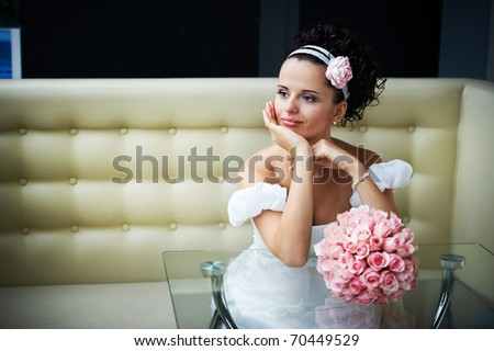 Portrait beautiful bride with bouquet of flowers on modern interior in wedding day