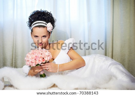 Portrait beautiful bride with bouquet of flowers on white bed in wedding day