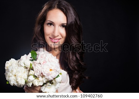 Portrait beautiful brunette woman poses with bouquet of white flowers. Fashion photo in studio.