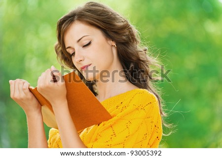 portrait beautiful gay long-haired woman reading book background summer green park