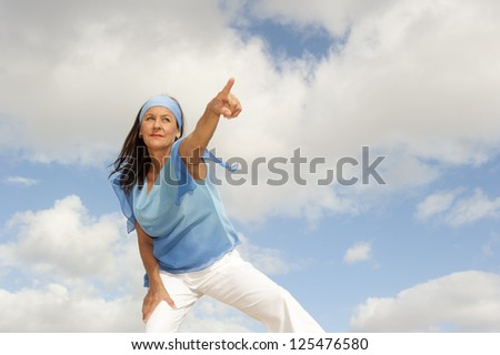 Portrait beautiful looking middle aged woman confident, determined and successful smiling, focused pointing finger, isolated with cloudy blue sky as background and copy space.