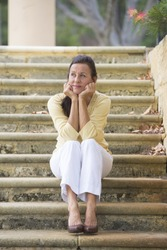 Portrait beautiful mature woman sitting outdoor on wide limestone steps in park, looking sad and lonely, depressed and stressed, with copy space and blurred background.