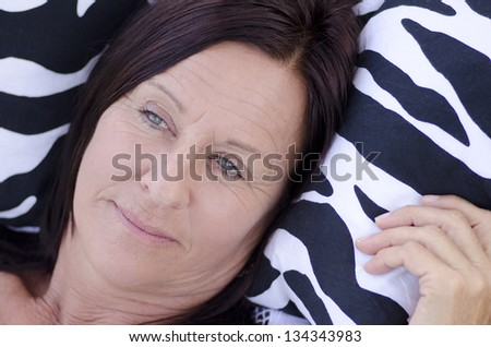 Portrait beautiful mature woman  with sad and lonely facial expression, lying alone and thoughtful on cushion.