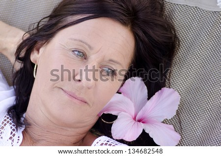 Portrait beautiful mature woman  with sad and lonely facial expression, lying alone and thoughtful with flower on hammock.