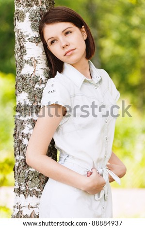 portrait beautiful sad woman leaning wood background summer green park
